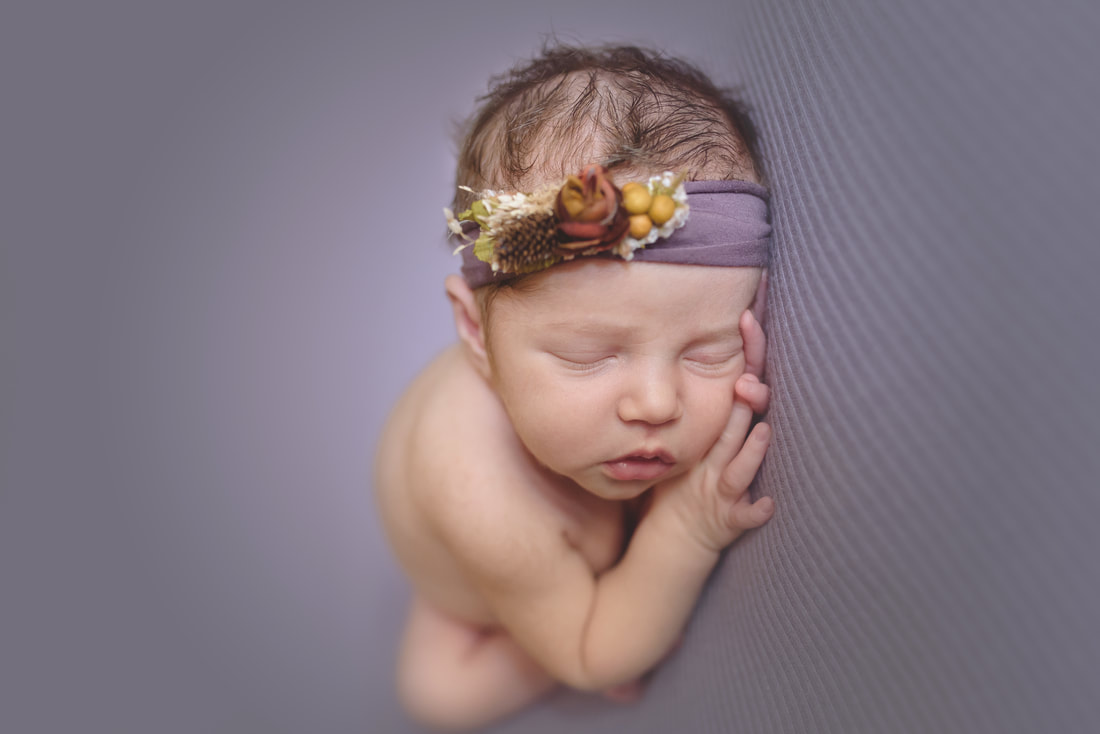 Baby girl posed on purple blanket wearing a flower headband at her newborn session with