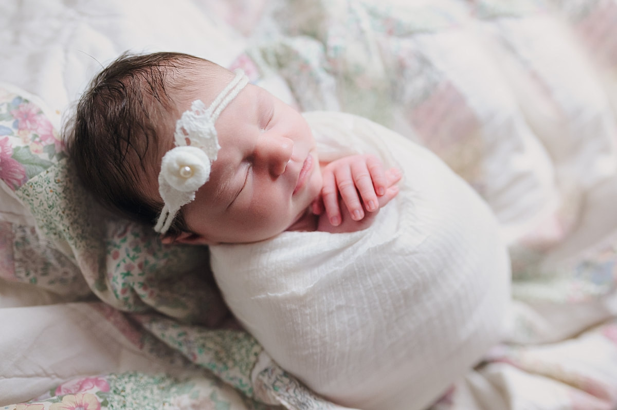 Newborn photo session baby girl swaddled in a white blanket sleeping on a vintage
