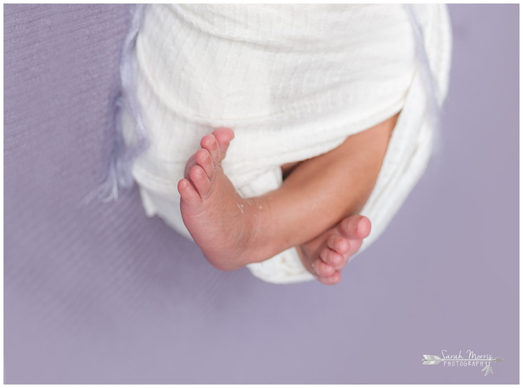 newborn photos of baby girl feet on purple blanket