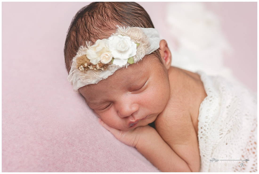 newborn photos of baby girl on pink blanket wearing flower headband