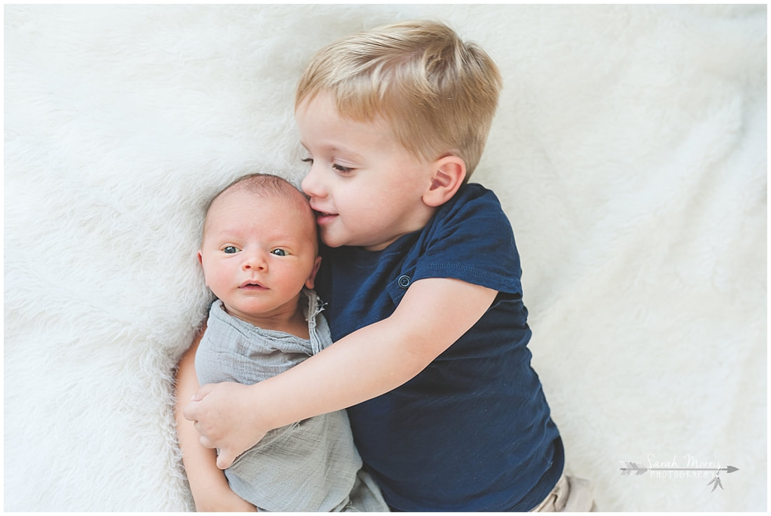 Newborn photos with older siblings on fur rug
