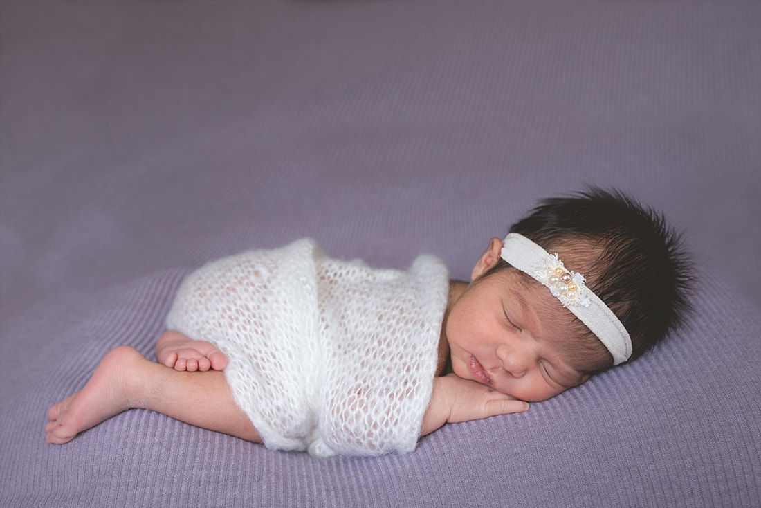 Newborn baby girl posed on a purple blanket and wrapped in a cream knit blanket at
